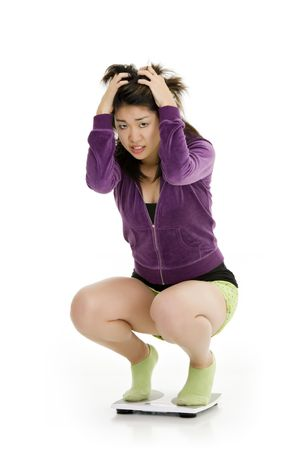 weighting: Beautiful Asian teenager weighting herself and upset by it