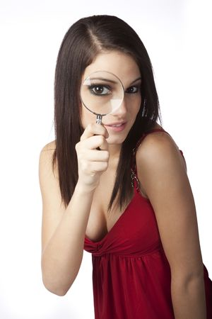 Beautiful Caucasian woman holding a magnifying glass up to her eye photo