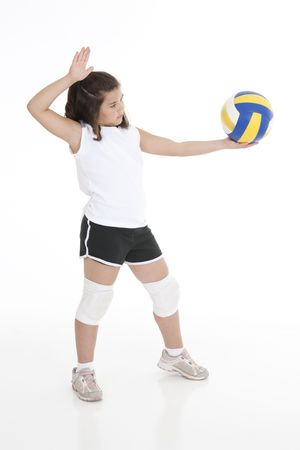 indoors: Cute Caucasian girl serving the ball in volleyball Stock Photo