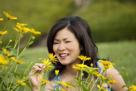 Beautiful Asian woman enjoying a field of daisies photo
