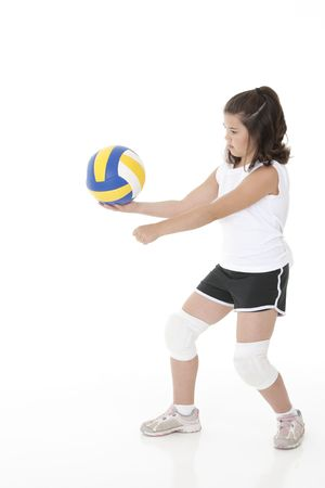 sportingly: Cute Caucasian girl serving the ball in volleyball Stock Photo