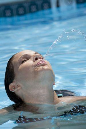 spitting: Beautiful Caucasian woman enjoying a day at the pool Stock Photo