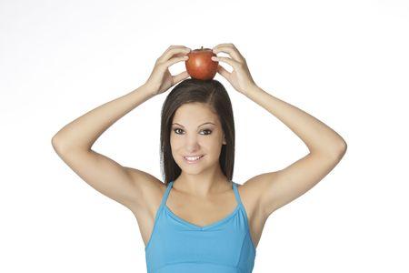 early 20s: Mujer blanca, hermosa en su 20 a�os con una manzana en la parte superior de la cabeza. Concepto de comer alimentos sanos