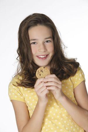 junk: Cute Caucasian girl eating Chocolate Chip Cookies Stock Photo