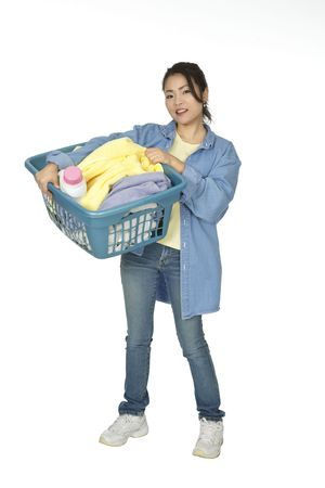 Cute Asian woman holding a basket of laundry photo