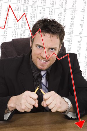Caucasian businessman setting at a desk and looking very angry and frustrated because of the Stock Market Stock Photo - 5533969
