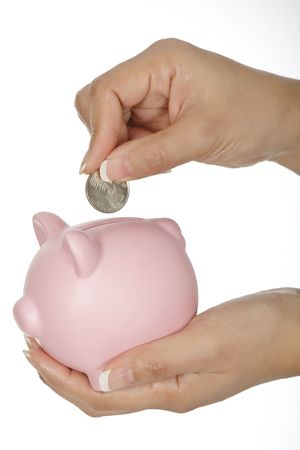 Woman holding a piggy bank and placing a quarter into it photo