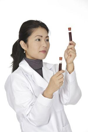 tecnico laboratorio: T�cnico de laboratorio de Asia hermoso examinar un tubo de sangre Foto de archivo