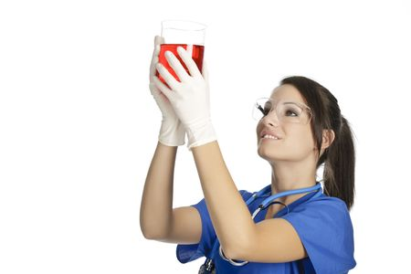 studing: Beautiful Caucasian woman working as a laboratory technician studing a beaker of red liquid Stock Photo