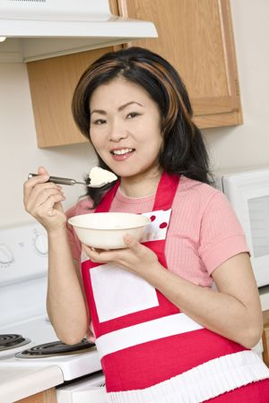 Beautiful Asian woman eating ice cream with in the kitchen photo