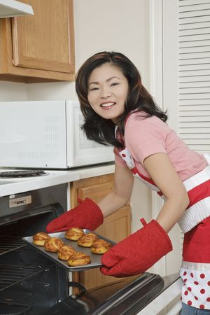 Beautiful Asian woman baking Cinnamon Rolls photo