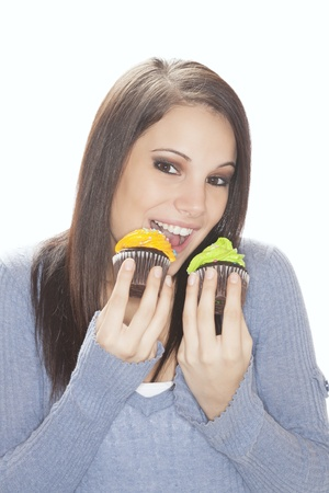 Beautiful Caucasian woman eating very unhealthy cupcakes photo