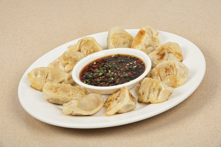 sause: Homemade Chinese dumplings with dipping sause. Also known as Pot Stickers. Also has a clipping path.