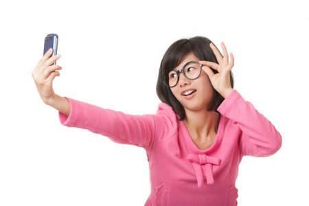 A beautiful Chinese woman using a cell phone to take a selfie on a white background Stock Photo