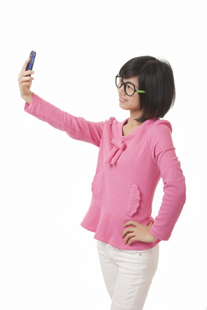 A beautiful Chinese woman using a cell phone to take a selfie on a white background photo