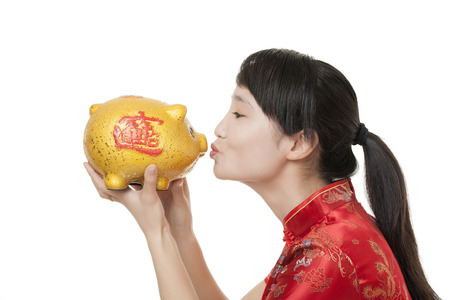 Beautiful Chinese woman wearing a traditional dress known as a Chipao holding a piggy bank photo