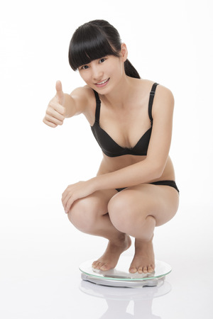 slender: Beautiful Chinese woman weighing herself on a scale and excited with the results isolated on a white background