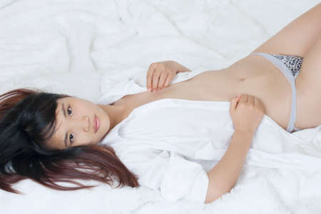 woman panties: Beautiful and sexy Chinese woman wearing a white shirt isolated on a white background