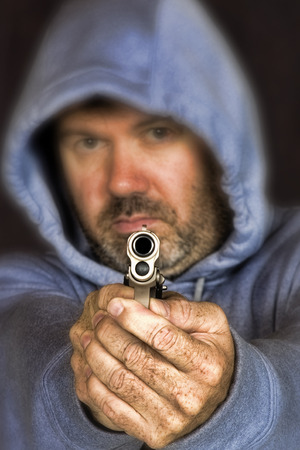 confrontational: Thief or gang member holding handgun in a threatening position Stock Photo