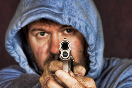 confrontational: Thief or gang member holding a handgun in a threatening position Stock Photo