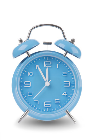 running out of time: Blue alarm clock with the hands at 5 minutes till 12 illustrating time is running out isolated on a white background