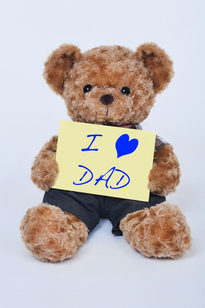 day care: A cute teddy bear holding a yellow sign that says I love dad for Fathers Day isolated on a white background