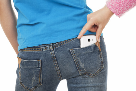 Sexy woman with a cell phone in her back pocket and a thief in trying to steal it on a white background photo