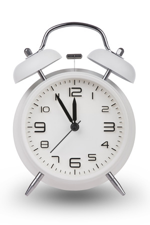 running out of time: White alarm clock with the hands at 5 minutes till 12. Illustrating Time is Running Out isolated on a white background
