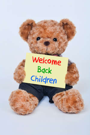 bears: Cute teddy bear holding a yellow Welcome back children sign isolated on a white background