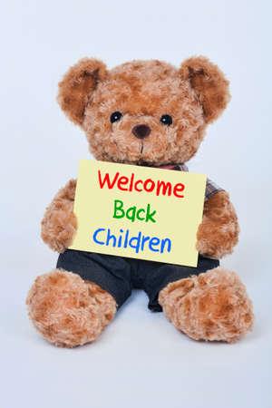 oso de peluche: Lindo oso de peluche que sostiene una amarilla Bienvenido de nuevo los niños firman aislado en un fondo blanco
