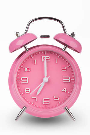 pm: Pink alarm clock with the hands at 7 am or pm isolated on a white background.
