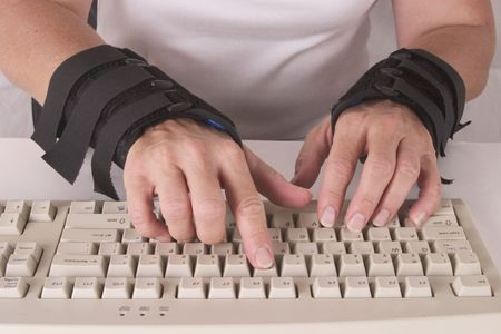 carpal: womans hands in wrist braces typing
