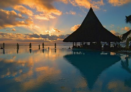 bronzed: Pool and bar silhouetted against a spectacular sunset Stock Photo