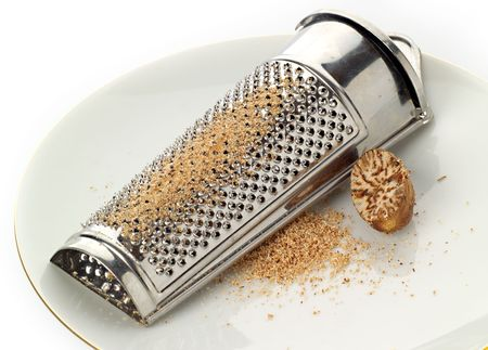grater: Nutmeg and grater on a plate, with freshly ground spice