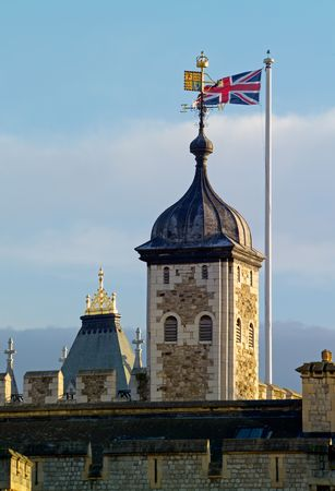 ancient prison: Tower of London detail, with the Royal Standard and Union Flag.  Focus on Royal Standard and Union Jack. Stock Photo