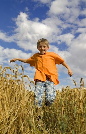 happy running boy in barley field.  Focus on boy's face. Stock Photo - 2060386