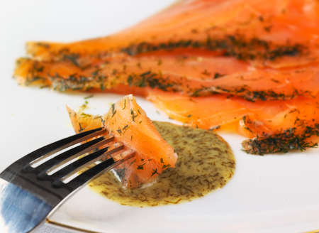 dipped: Gravadlax with dill sauce, fish being dipped in the sauce