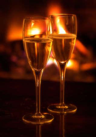 log fire: Due flauti champagne illuminata da fuoco a legna. Soft focus.  Archivio Fotografico