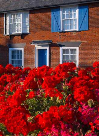 brich: Red Gereniums, blue shuttered red brich house