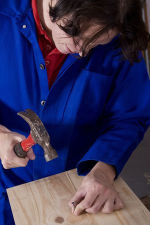 overall: Dark haired man with blue overall hitting nail with hammer