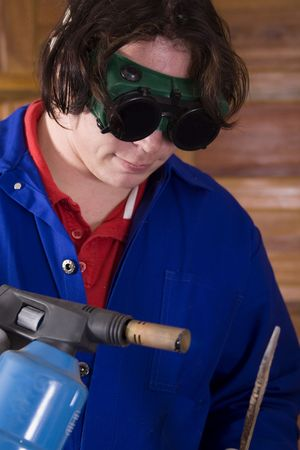 overall: Dark haired man with blue overall holding blowtorch and metal