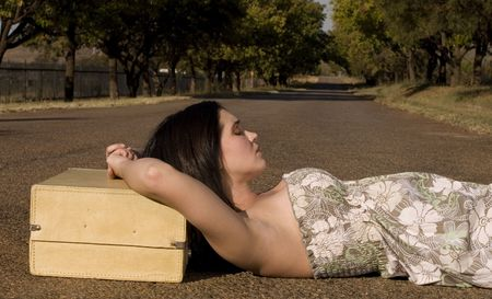 Brunette lying on her suitcase in the middle of the road wearing day dress Stock Photo - 943420