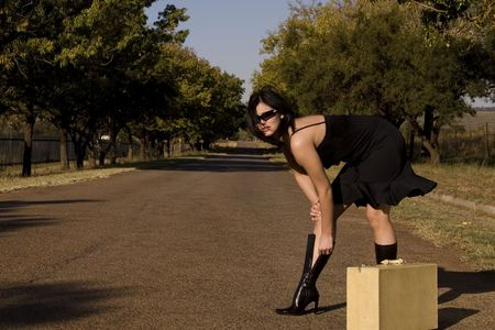 persuade: Attractive brunette trying to persuade motorists to give her a lift unzipping boots
