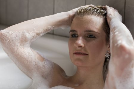 bathtime: Attractive blond woman lying in bubble bath looking at the camera