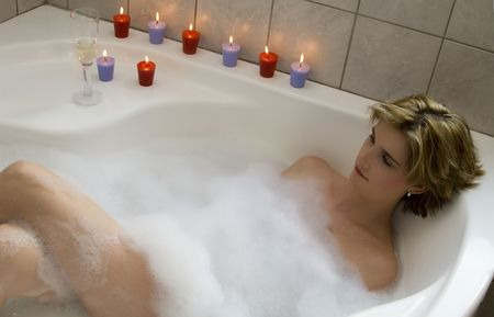 lying in bathtub: Attractive blond woman lying in bubble bath with several candles and champagne