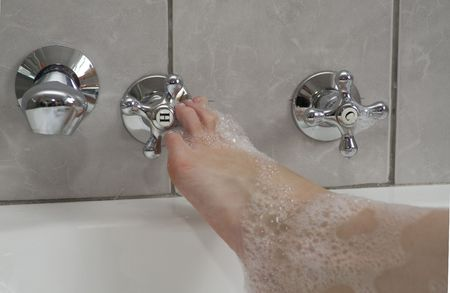 hot water tap: Womans boot adjusting the hot water tap in a bubble bath Stock Photo