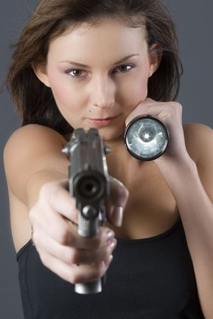 Attractive brunette pointing handgun towards camera with a flashlight photo