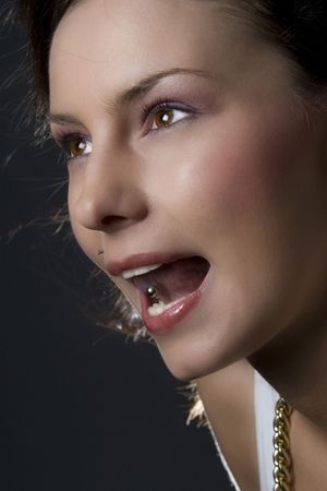 Attractive young woman sticking out her tongue to show piercing