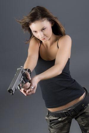 Attractive brunette pointing handgun towards camera