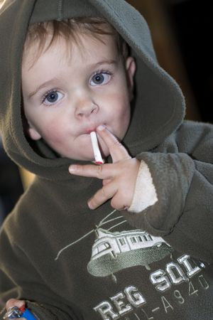 Young boy smoking a cigarette sweet while looking at the camera